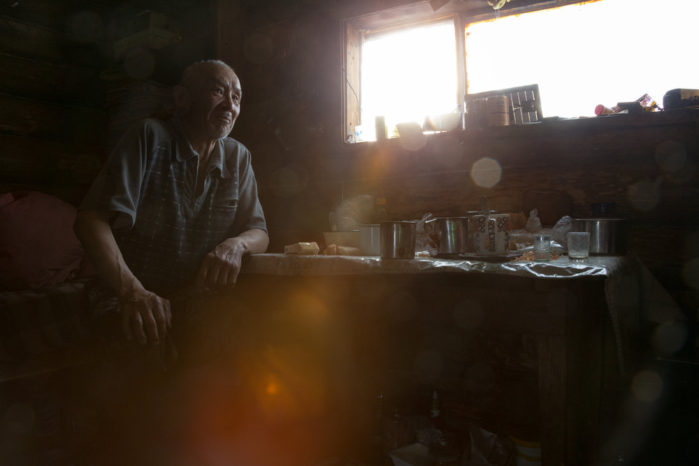 An ethnic Even man sits on his bed in his one room cabin in the backcountry. Bystrinsky District, Kamchakta, Russia.