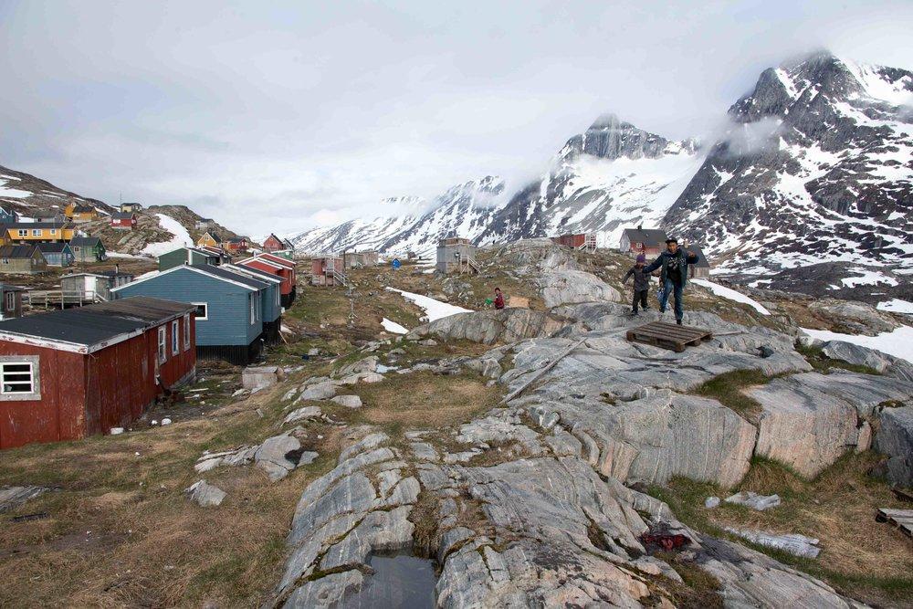 Kids run through the Greenlandic settlement of Kuummiit.