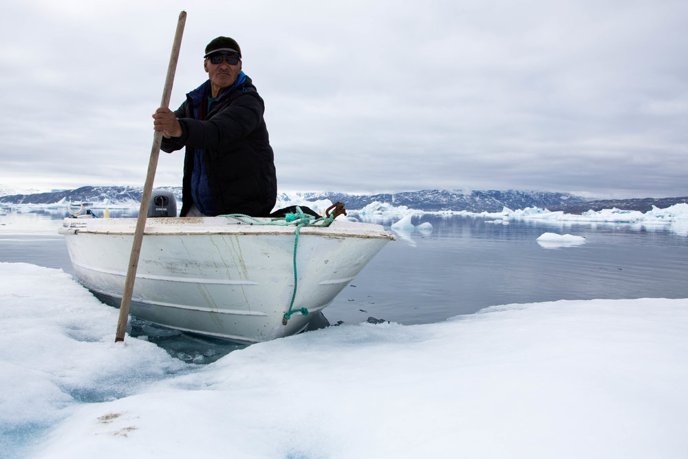 A local seal hunter anchors his boat to an iceberg with a pointed spear to collect fresh drinking water straight from the ice.