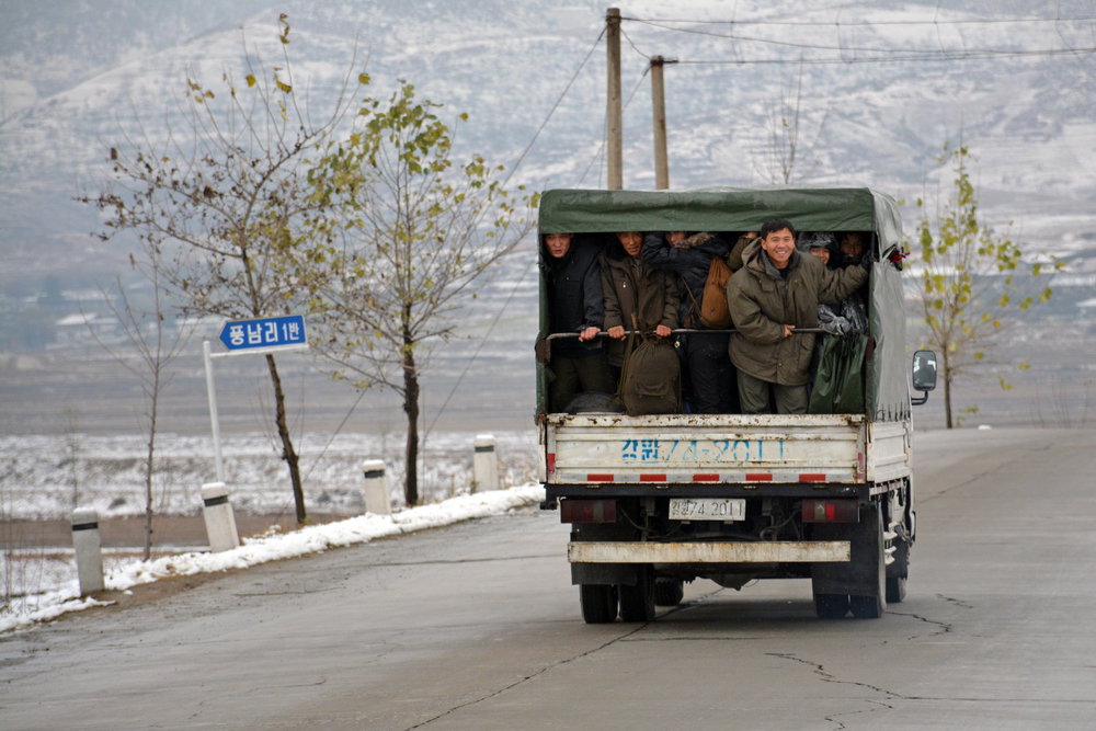 A group of people ride in the back of a truck outside of Wonsan.