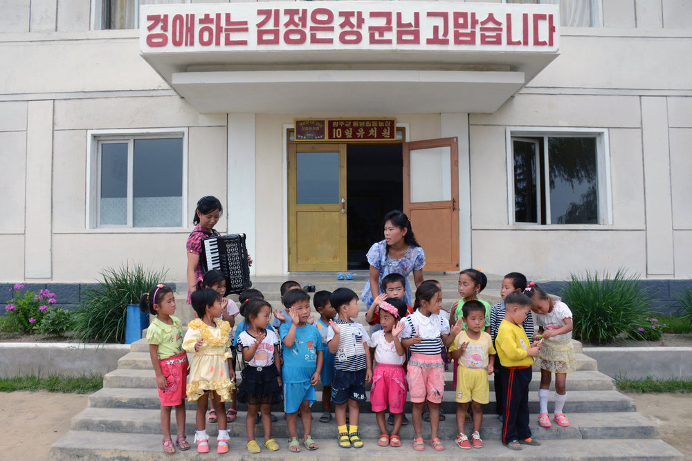 Kindergarteners wave goodby outside their school in Hungnam, South Hamgyong Province, North Korea.