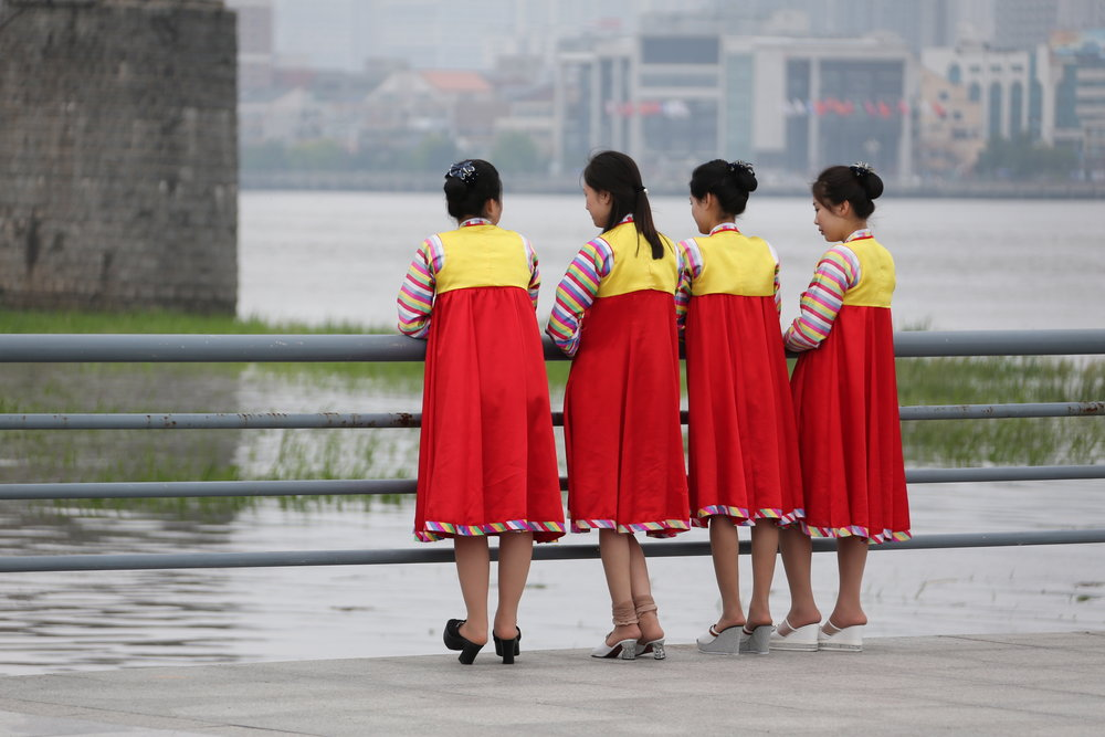 North Korean women in Sinuiju stand by a railing underneath the Friendship Bridge connecting the DPRK to Dandong, China. China is visible in the background.