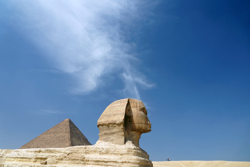 A group of tourists is dwarfed by the Great Pyramid and Sphinx in Giza, Egypt.