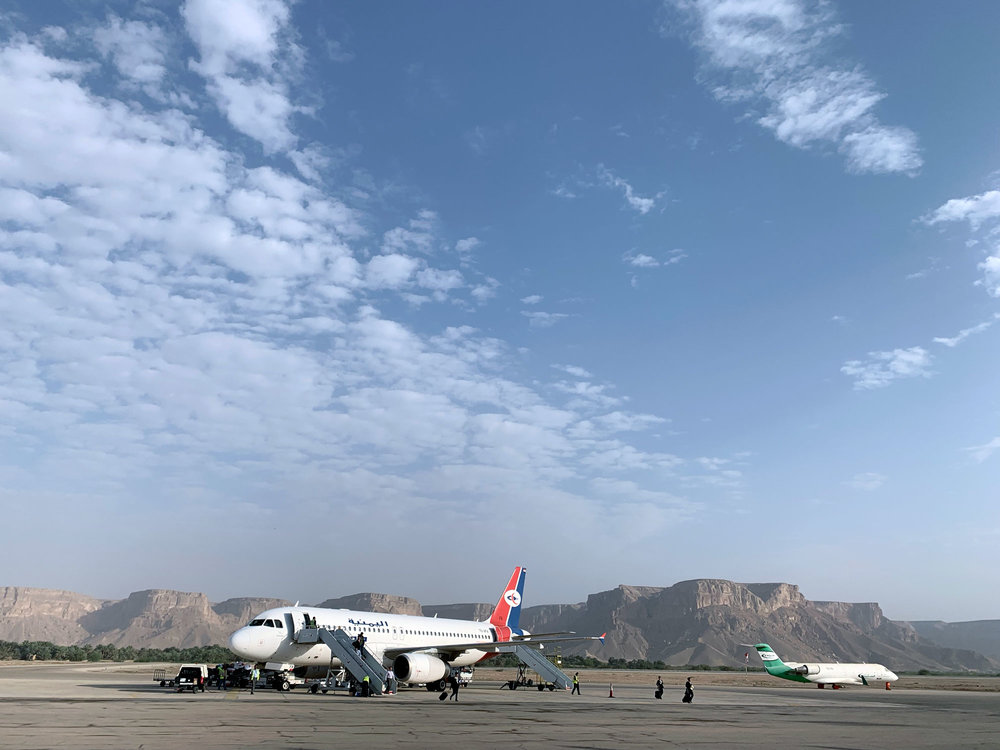 Our Yemenia plane parked at Seiyun Airport waiting to take off again for Socotra. A broken Felix Airways plane is on the right.