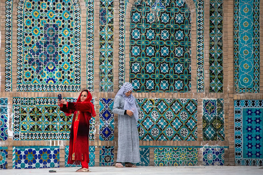A girl poses for a selfie at the Blue Mosque in Mazar-i Sharif. Cell phones are extremely popular amongst middle class and urban Afghans and they particularly love using social media apps like Facebook and WhatsApp.