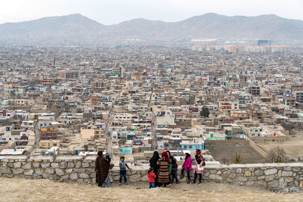 A Kabuli family takes a look over the city of Kabul from Bibi Maroo Hill in central Kabul. Kabul is surrounded by the Hindu Kush mountains and as the city grew, many neighbourhoods simply expanded onto the mountain faces.