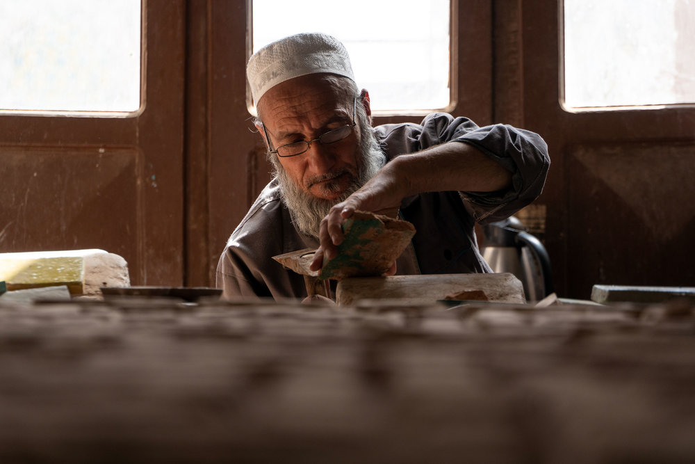 Afghanistan's far western city of Herat lies close to the country's borders with Iran and Turkmenistan. The city is culturally very Persian, and was a major trading post on the Silk Road. It is also famed for its artisans, especially the tile work. This man is using a pick to shape a coloured tile in the Timurid style. Herat's Friday Mosque has its own tile production and mosaic production factory.