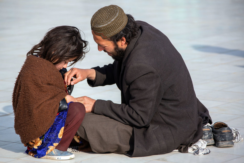 A father helps his daughter with her clothes in Mazar-i-Sharif.