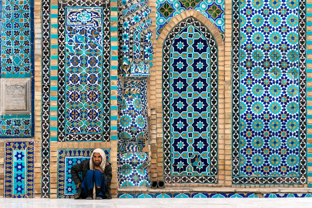 A man takes a rest against a colourful mosaic wall at the Blue Mosque in Mazar-i-Sharif.