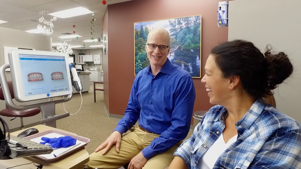 Dr. John Murray meets with a patient and shows how her teeth will look after Invisalign treatment.