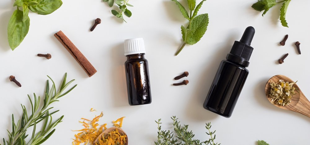 Two-bottles-of-essential-oil-with-a-selection-of-herbs-on-a-white-background.jpg