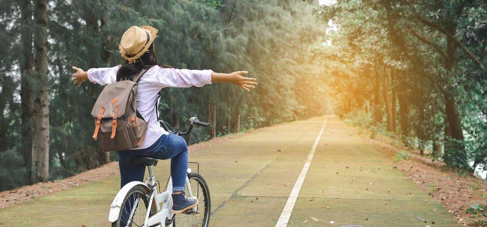 Women-soaking-up-the-sun-biking-in-the-woods.jpg