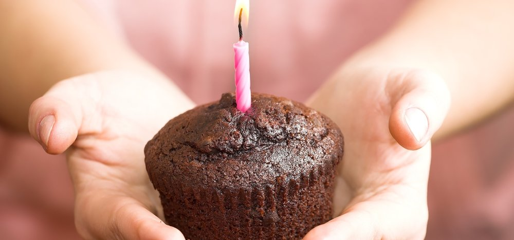 girl-holding-birthday-cupcake-at-party.jpg