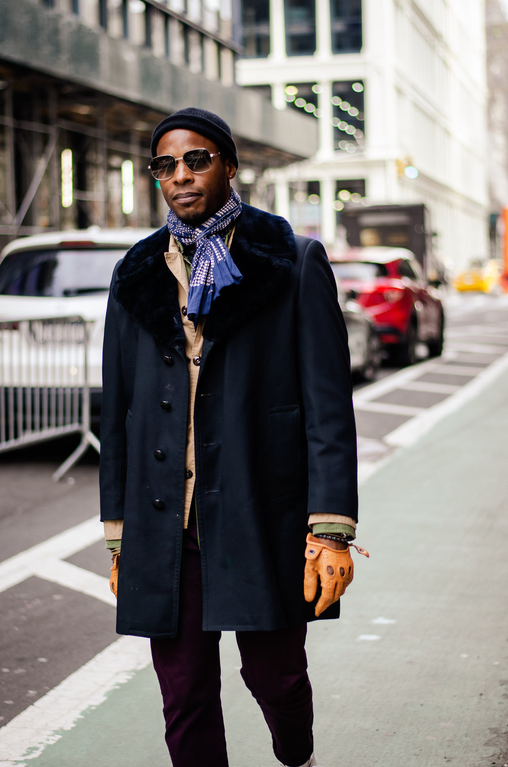 As a visual merchandiser, Raza understands the power of the accessory: The beanie, sunglasses, lightweight scarf, and driving gloves overlook the fact that he's wearing a simple mink-collared jacket.