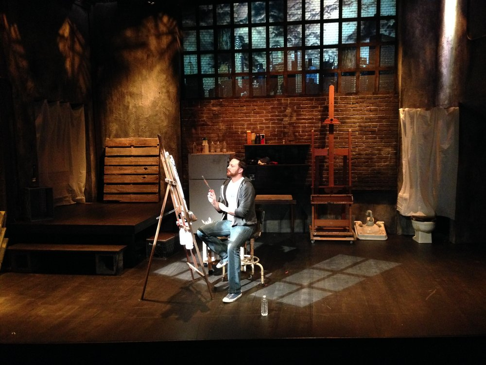 "Now the set is nearly ready.  All the ""tech"" aspects of the play are coming together.  Lighting is being placed and focused.  The photos are being projected, and this photo of ""Hugh"" (Coronado Romero) is where he starts the play."