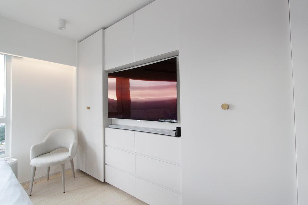 Master Bedroom | Built-in TV niche with sliding doors to wardrobe.