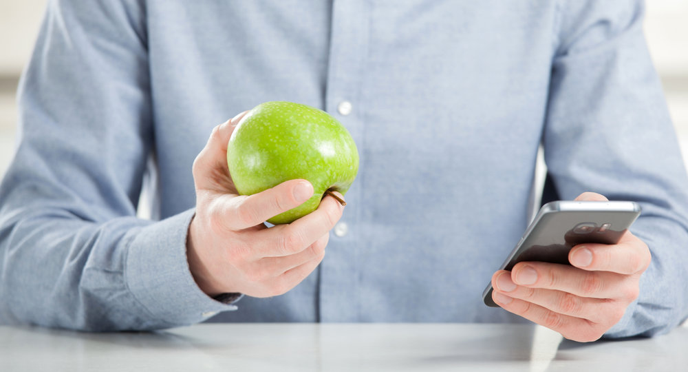 stock-photo-unrecognizable-young-man-eating-fresh-green-apple-and-using-his-smartphone-667970344.jpg