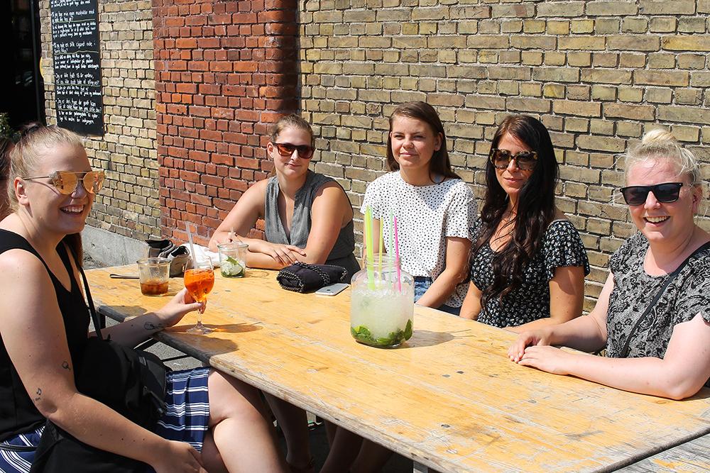 STORMS PAKHUS: Disse søte damene sitter i sola og bare deler en bitteliten drink ... Foto: Tenk Koffert