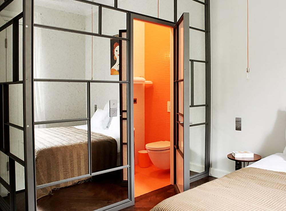 KULT HOTELL: Veggen inn til det knalloransje badet hos Between Us B & B er av speil. Og lobbyen på hotellet blir til et kult utested på kvelden. Foto: Hedda Bjerén