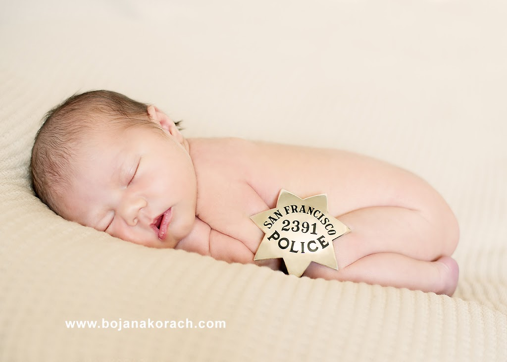 newborn baby girl sleeping and a san francisco police badge, newborn photography