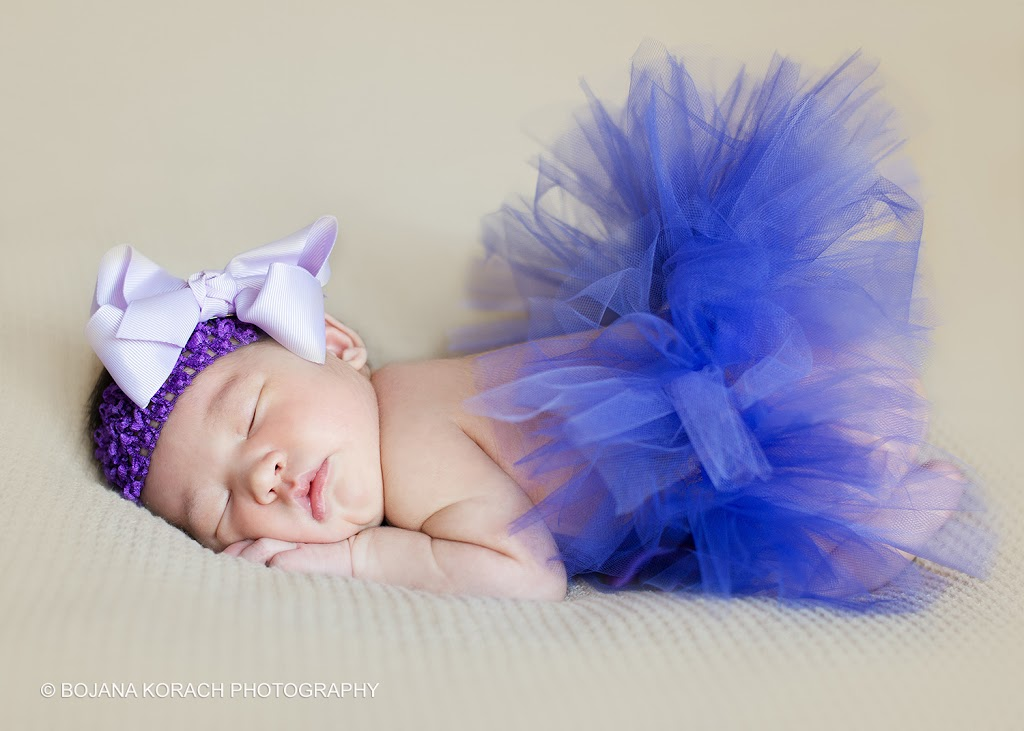 newborn baby girl with a headband and a purple tutu sleeping and posing for a best walnut creek photographer
