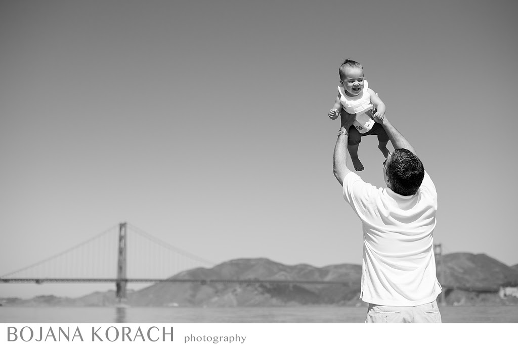 father holding his daughter up in the air on crissy field beach in san francisco, photography