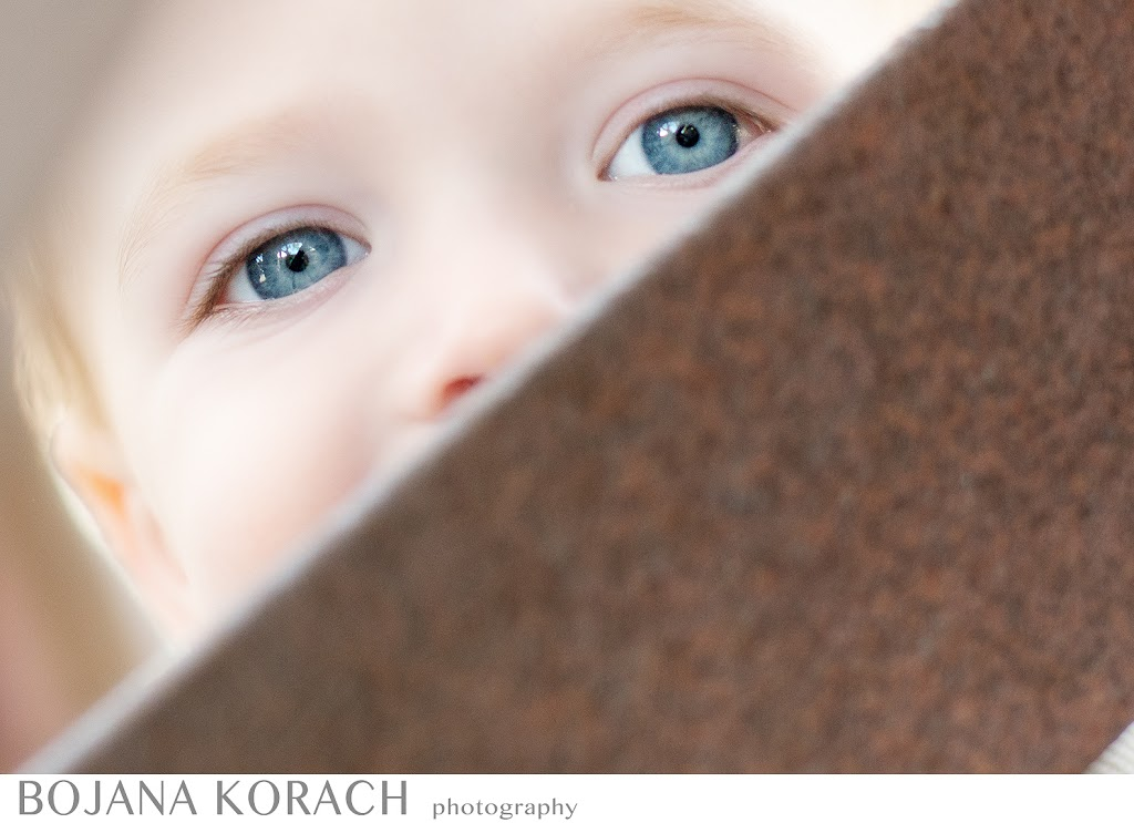 blue eyes of a one year old baby boy hiding behind a tractor wheel at the old borges ranch in walnut creek photography by best east bay baby photographer