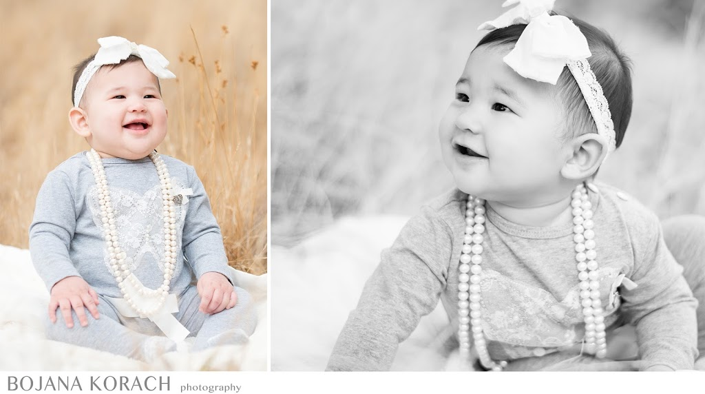 beautiful baby girl sitting in a field and wearing pearl necklace and a white bow photography by best walnut creek photographer