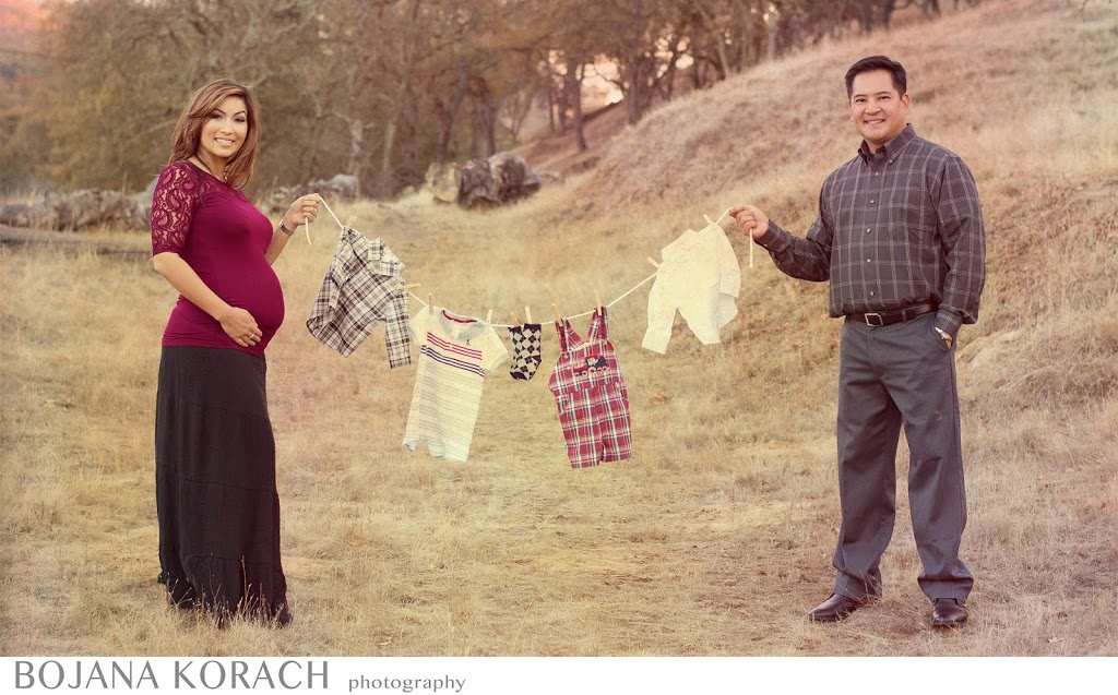 expectant couple is holding a hang wire with baby clothes in walnut creek, maternity photography