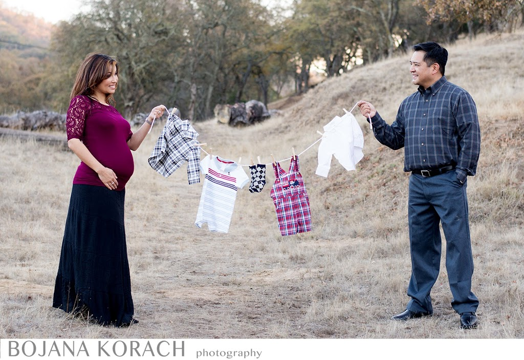 walnut creek maternity, expectant couple holding a string with baby clothes hanging