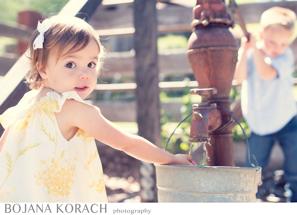 San francisco bay area family photography, brother pumping water for his sister in a beautiful yellow dress