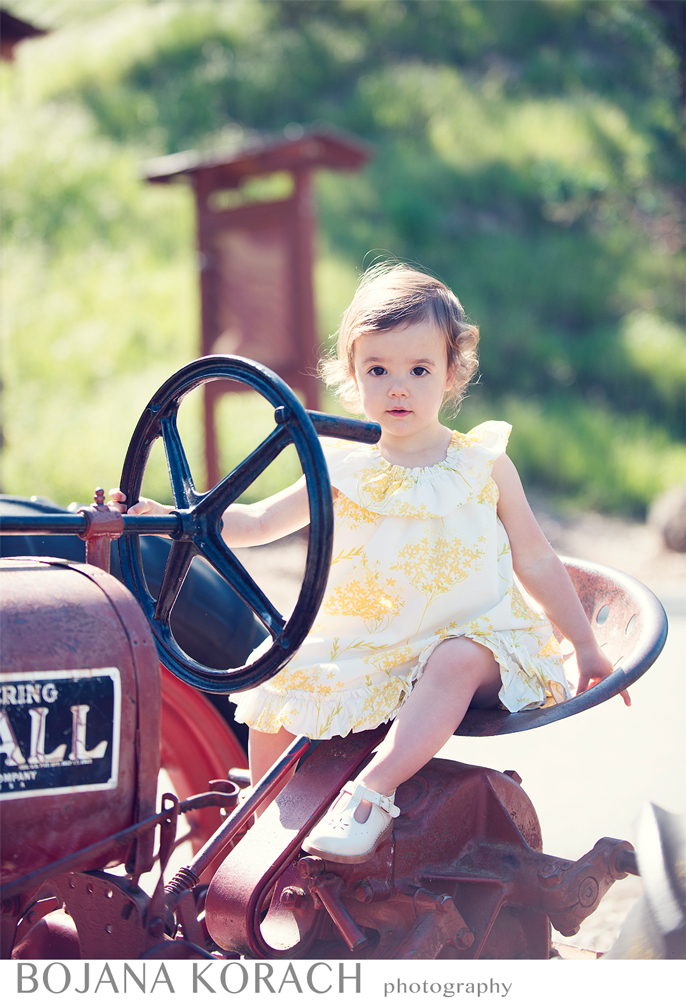San Francisco bay area photographer takes a stunning shot of a young girl sitting on a tractor and posing