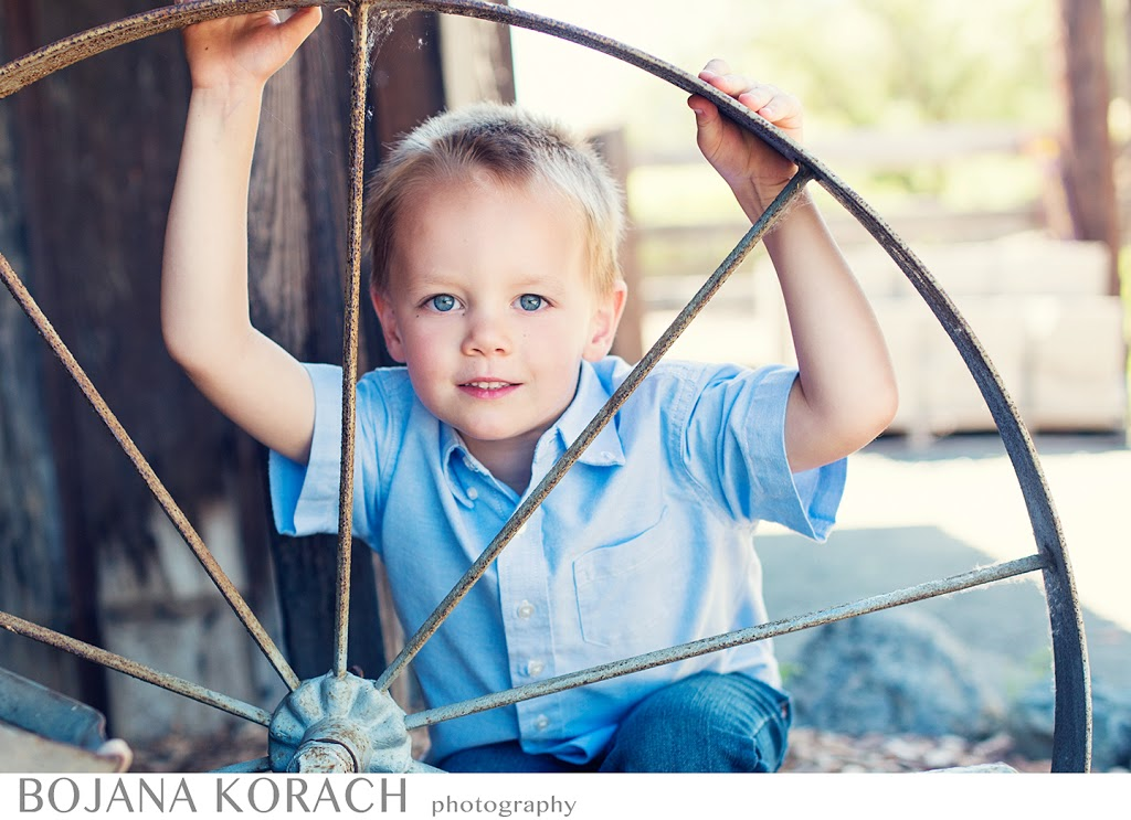 san francisco bay area photographer captures a four year old boy holding a wheel and posing for a portrait