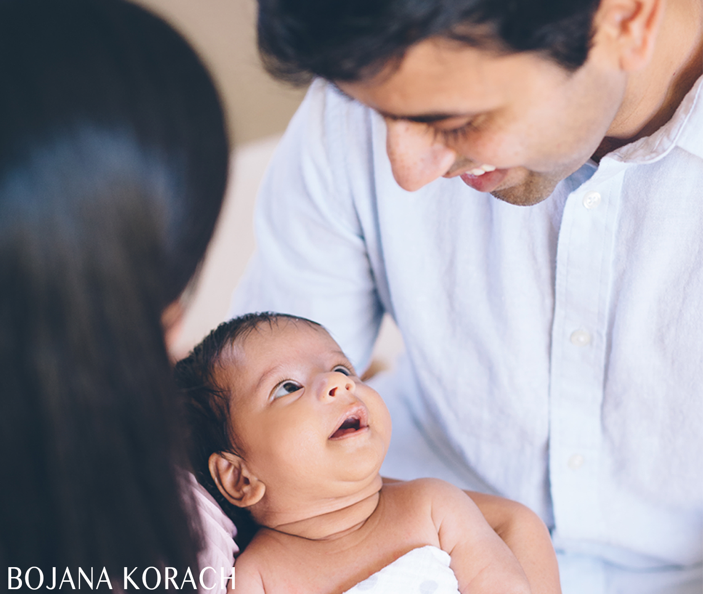 newborn baby boy looks lovingly at his father