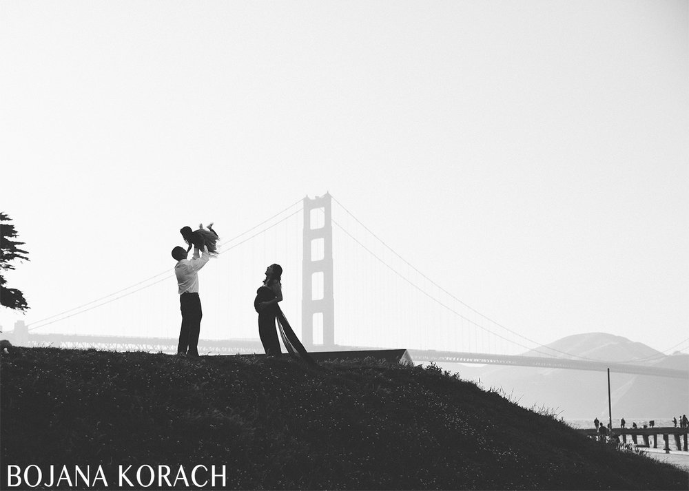 silhouette of a family expecting with golden gate bridge in the background