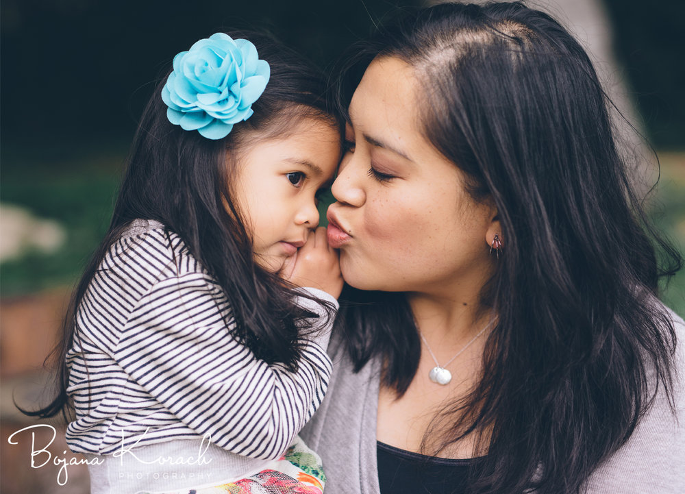 mother kissing her daughter during family photo session