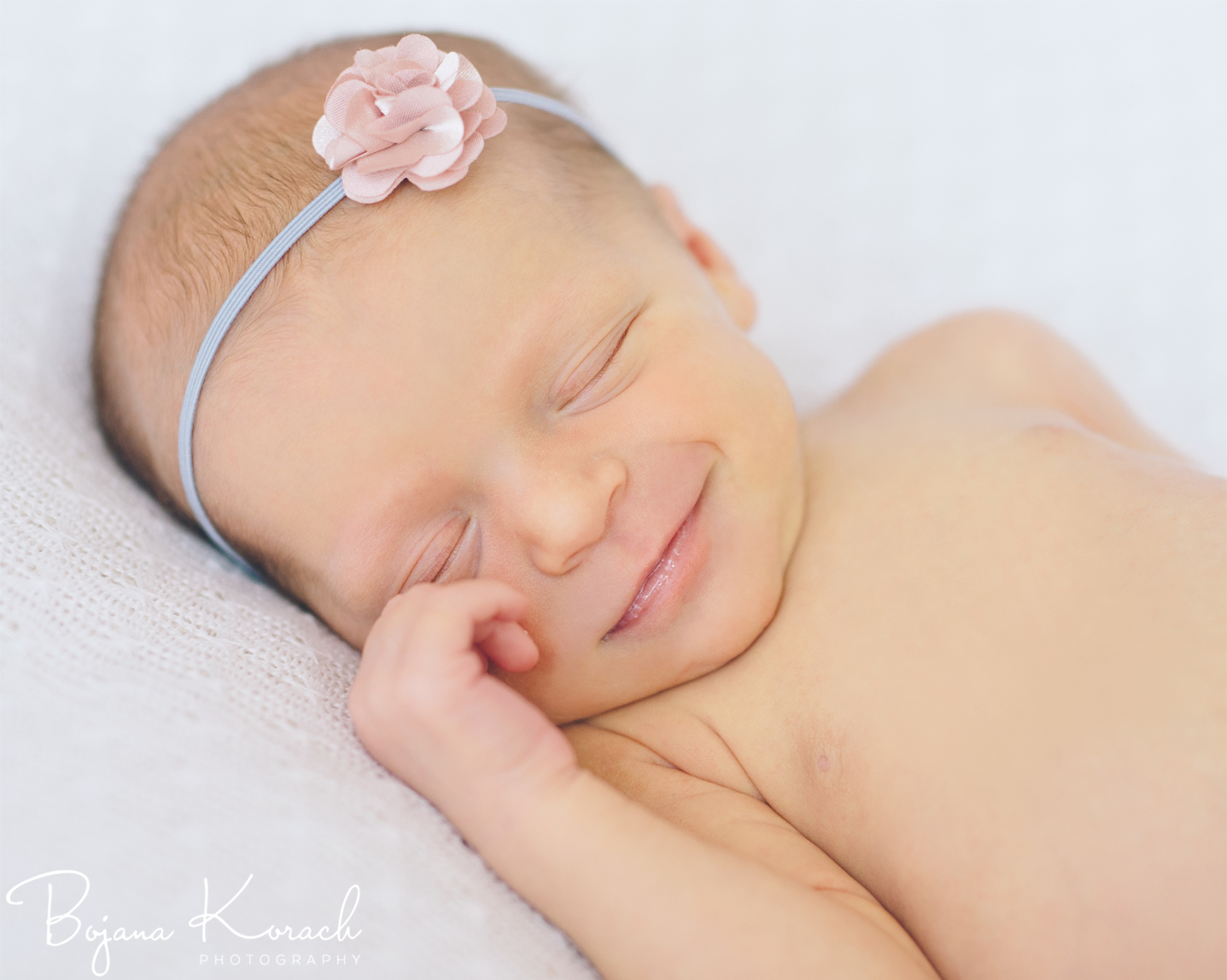 newborn baby smiling with a rose color headband
