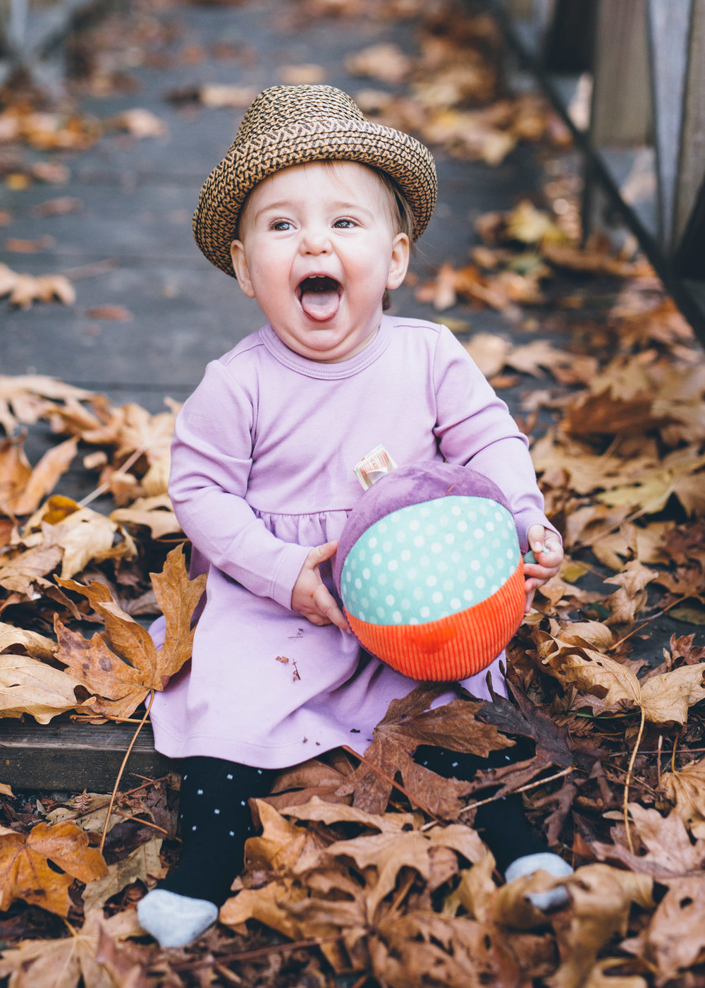 baby-wearing-a-hat-and-smiling-huge-with-a-ball-in-hands.jpg