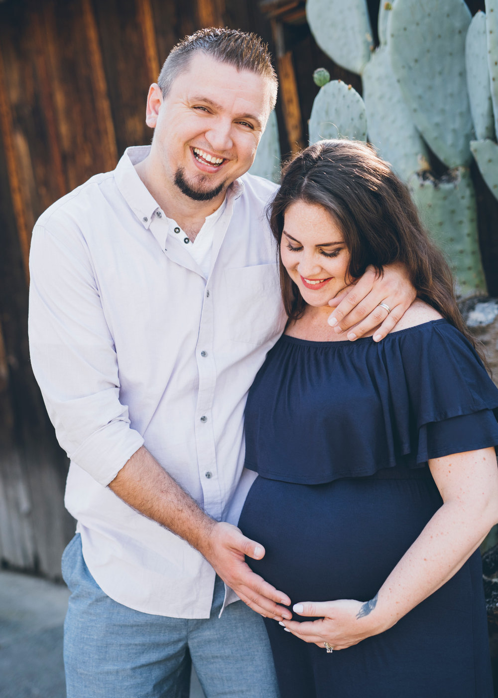 smiling-father-touching-his-wife's-pregnant-belly.jpg