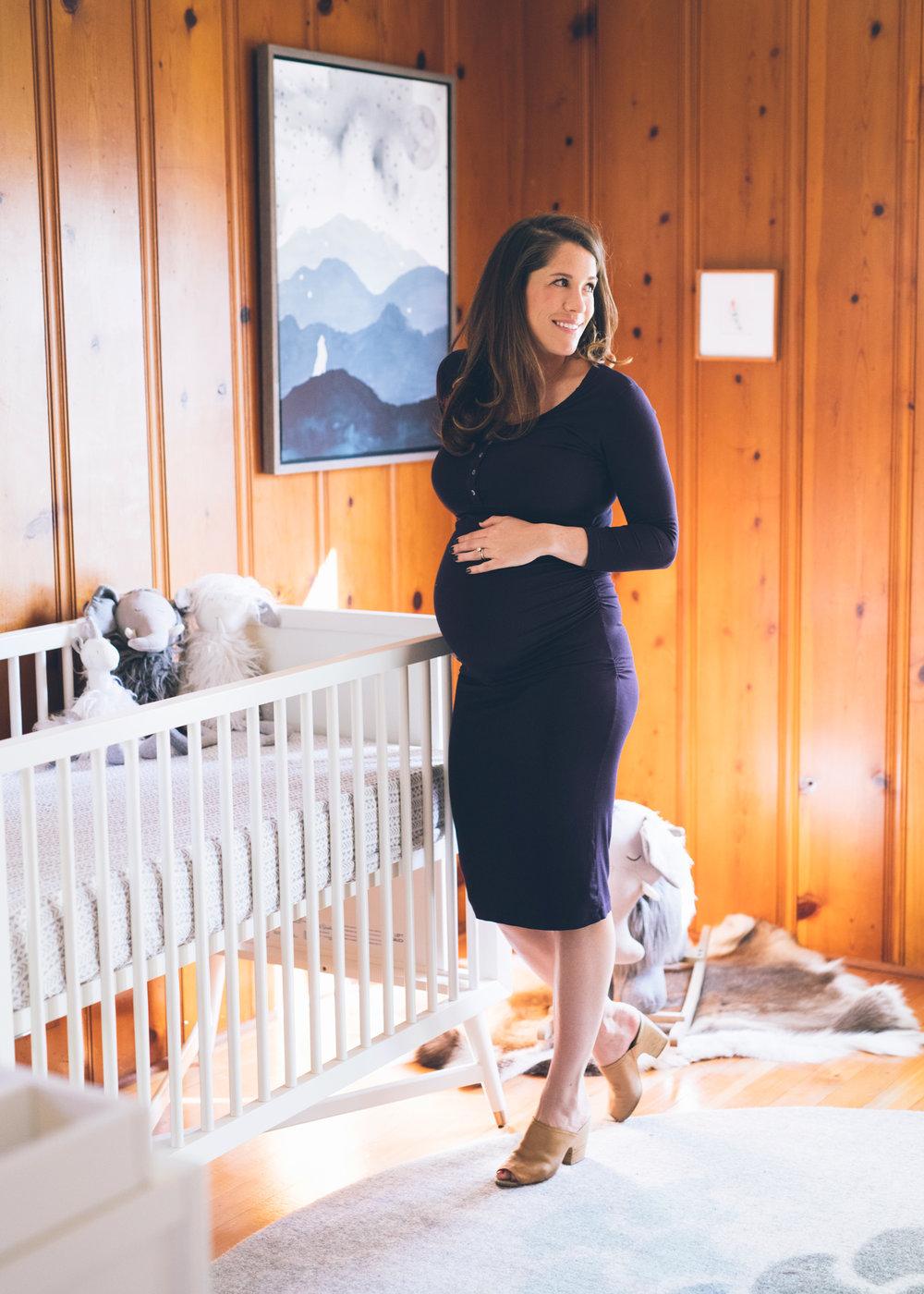 pregnant-woman-standing-near-a-crib-in-mid-century-modern-nursery.jpg