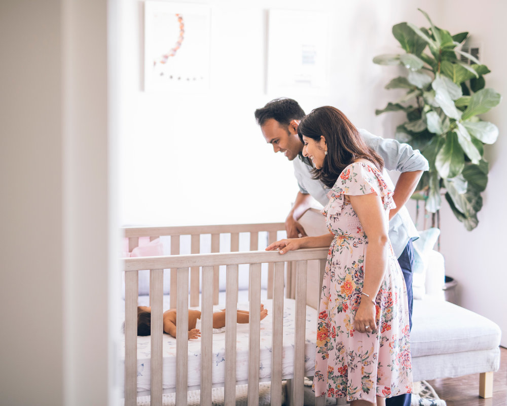parents-lovingly-looking-into-the-crib-in-their-san-francisco-apartment.jpg