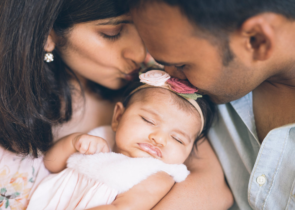 close-up-portrait-of-parents-kissing-their-beautiful-baby-girl.jpg