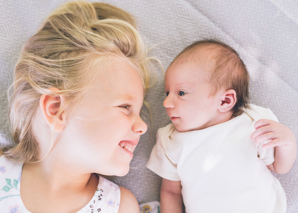 two-sisters-together-looking-at-each-other-during-lifestyle-newborn-portrait-session.jpg