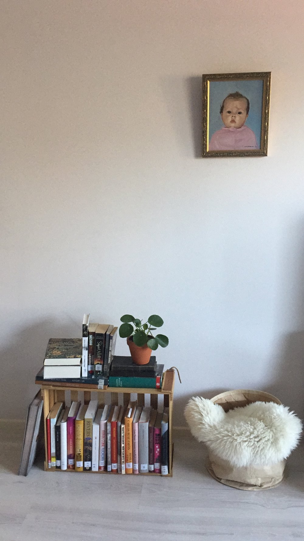 """Vär inredning följer ännu väldigt långt """"man tager vad man haver""""-konceptet. Här ser ni alltså väldigt extemporeinredning med tavlan på mig som barn (kallas även Mindy-Lisa) och min biblioteksbokshylla (trädgårdslåda). Att sånt."""