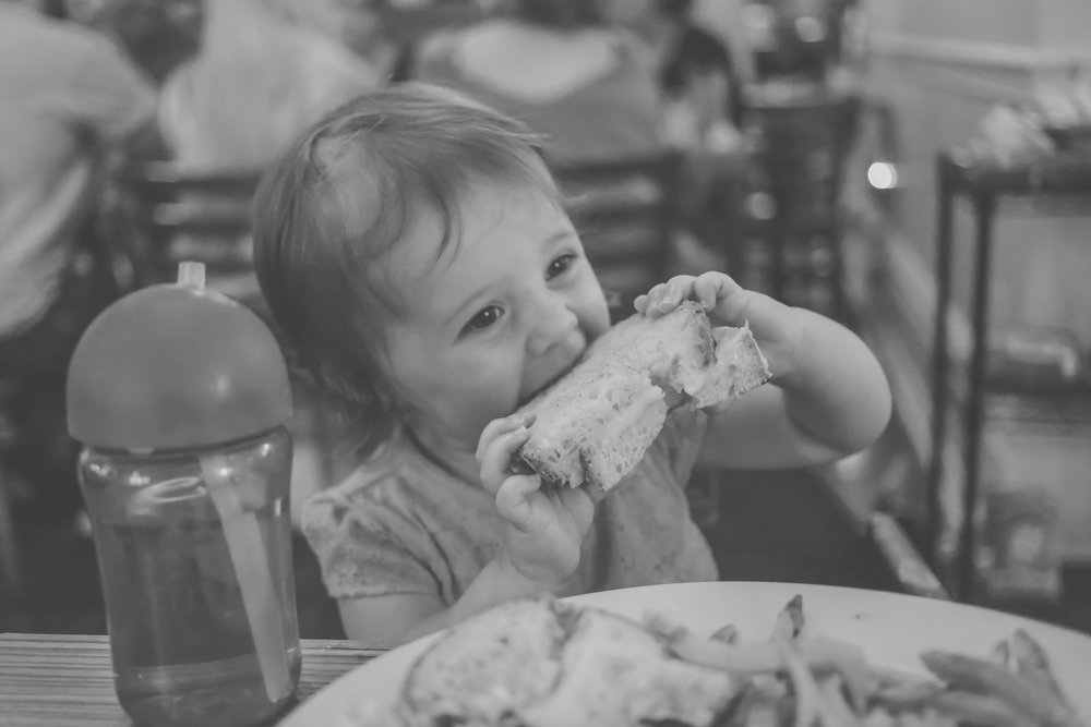 Toddler eating her grilled cheese at Sabrina's Cafe, Philadelphia, PA. Pennsylvania Family Photojournalism.