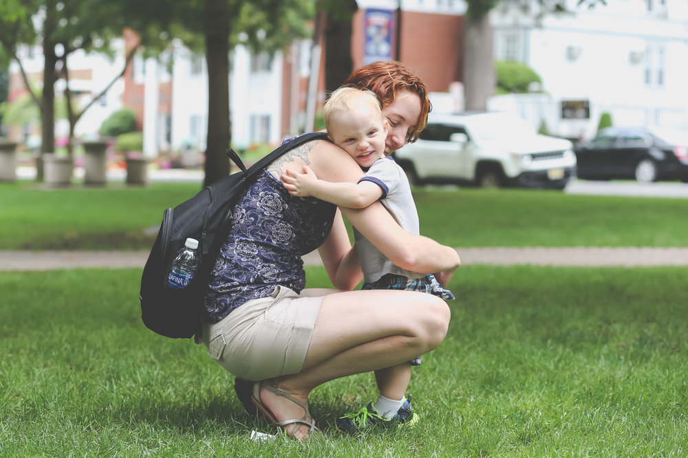 Toddler smiling and hugging mom at the park in Rutherford, NJ. Family photography by Jen Grima of Lehigh Valley, PA.