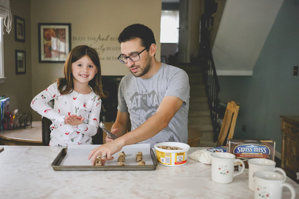 Smiling while baking Christmas cookies, holiday sessions by Jen Grima Photography, Family Photojournalism.