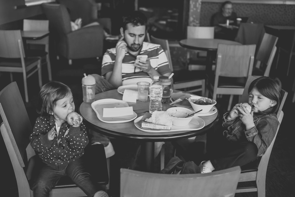 Father and daughters eating lunch at Panera Bread in Staten Island, NY. Documentary family photography.