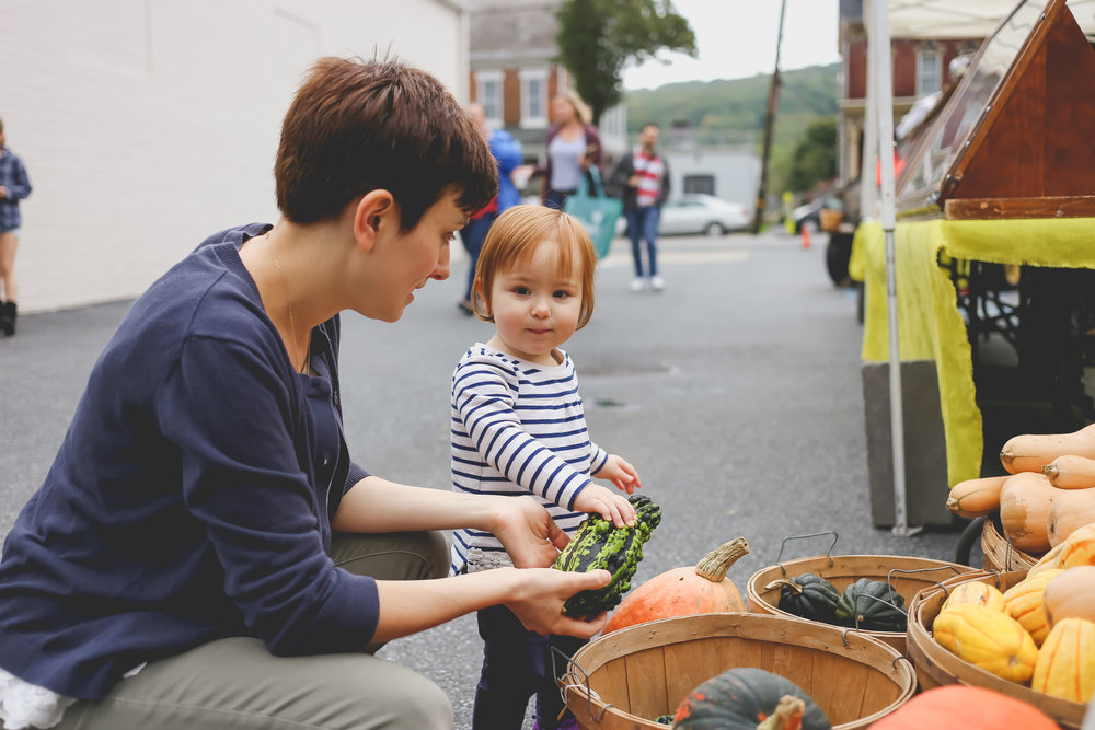 Toddler shopping for gourds with her mother at the Emmaus Farmer's Market. Lehigh Valley Family Photography.