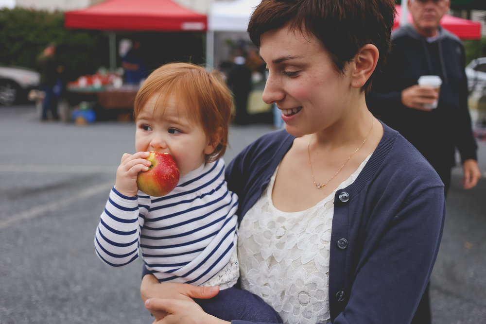 Daughter eating an apple with her mother at the Emmaus Farmer's Market. Documentary Family Photographer in Lehigh Valley, PA.
